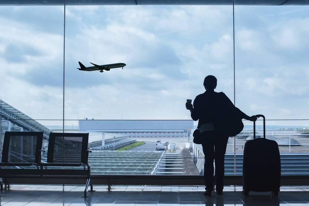 Frau steht mit Gepäck im Flughafen und beobachtet abhebendes Flugzeug.